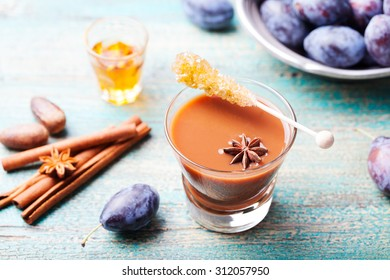 Plum hot mulled cider with fresh plums, rum, and spices on a turquois wooden background