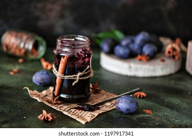 Plum jam in a glass jar with cinnamon and star anise, on a dark background, fresh plums. Selective focus.