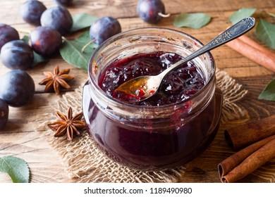 Plum jam in a glass jar. Fresh plum fruit on a wooden table