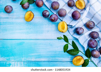 Plum slices and whole old worn wooden background close-up view from above. Plums on a swivel on a wooden table. Bright juicy background with place for text. Summer postcard.