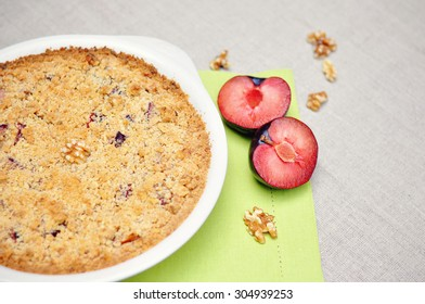 Plum tart, a pie with walnuts and juicy plums on a table, selective focus