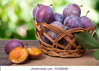 plum in a wicker basket on the wooden table with sackcloth and blurred green background
