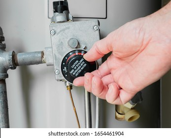 Plumber adjusting thermostat temperature dial on natural gas hot water heater. Residential boiler tank controls for heating household water.