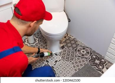 plumber applying silicone sealant around water closet