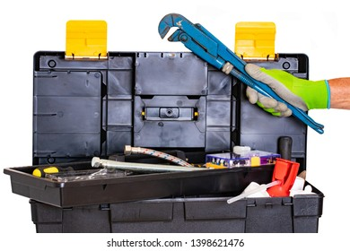 Plumber or carpenter tool box isolated. Black plastic tool kit box with assorted tools and a mans hand with a glove holds a big pipe wrench. Isolated on a white background.