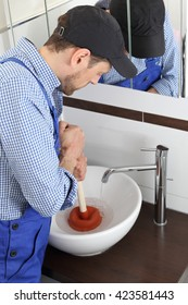 A Plumber cleaning a drain with a Suction rubber sucker cup
