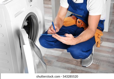 Plumber with clipboard near washing machine