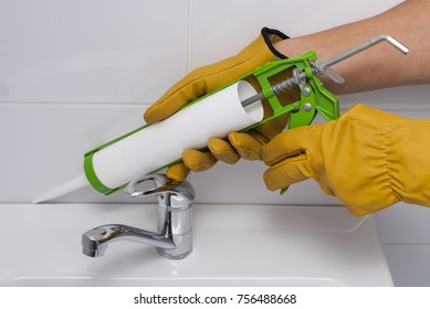 plumber fills the seam between the sink and the tile with a silicone sealant