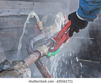 A plumber fixes a water leak on a water pipe.