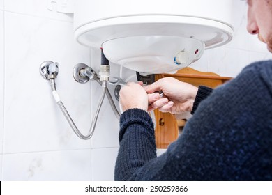 plumber fixing electric water heater