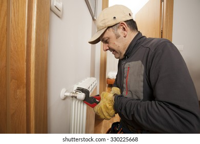 Plumber fixing a radiator in a house