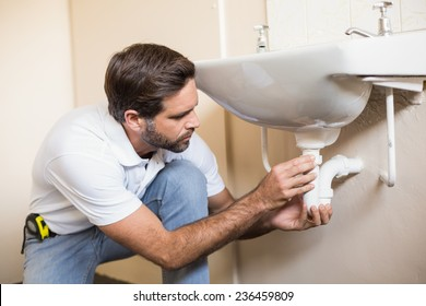 Plumber fixing the sink in a bathroom in a new house