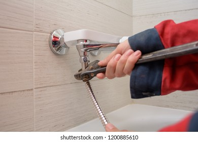 Plumber fixing water tap in a bathroom using spanner. hands fixing a shower faucet with a adjustable wrench.