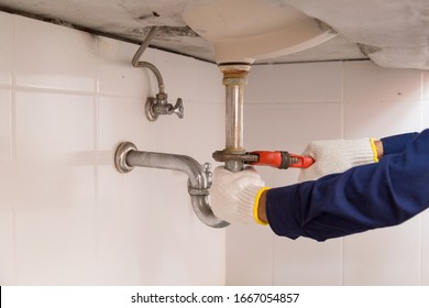 Plumber fixing white sink pipe with adjustable wrench.
