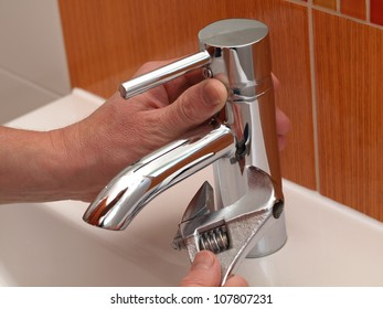 Plumber hands repair water tap with spanner