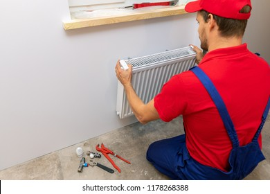 plumber installing heating radiator on the wall at home