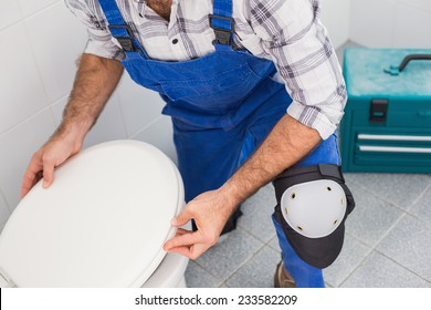 Plumber installing lid on toilet in the bathroom