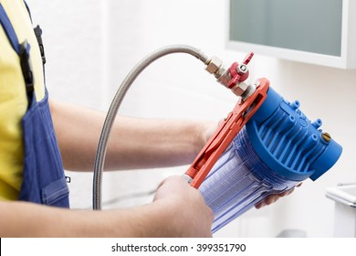 plumber installing new water filter in bathroom