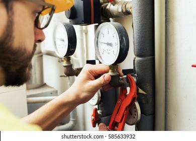 plumber installing pressure meter for house heating system