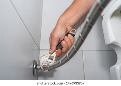 Plumber installs hose in a hard-to-reach place with an adjustable wrench.