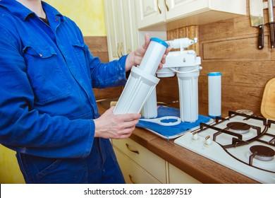 a plumber installs a water filter