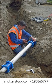 a plumber joins pipes at a large industrial building site