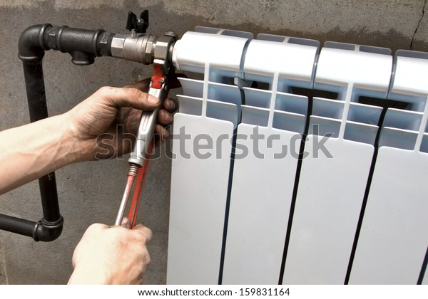 the plumber makes installation a heater radiator
