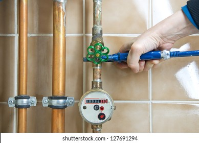 plumber with pliers and water clock