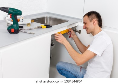 Plumber repairing the drain of a kitchen sink