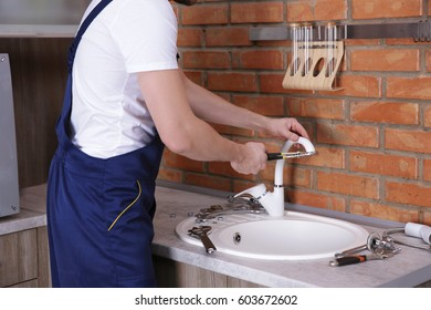 Plumber repairing faucet in kitchen, closeup