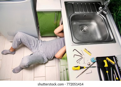 Plumber repairing the faucet of a sink in kitchen, man repair and fixing leaky old faucet, cartridge or mixer of the faucet, concept of repair and technical assistance, top view, kitchen overview