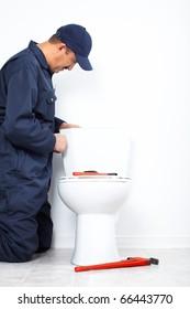 Plumber repairing a flush toilet