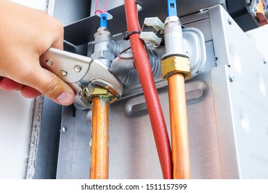 Plumber repairing a gas boiler of a heating home system in the boiler room. Close-up, selective focus.