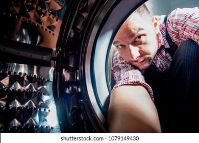Plumber repairing laundry machine in bathroom