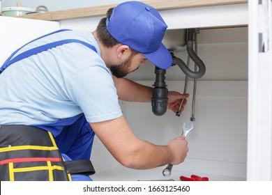 Plumber repairing sink in kitchen