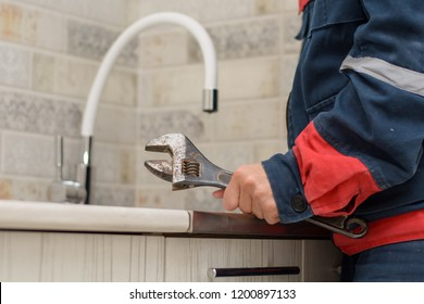 Plumber repairing tap at kitchen. plumber fixing a sink.Plumber man with tools in the kitchen. Plumbing and renovation.