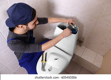 Plumber repairing toilet cistern at water closet