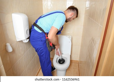 Plumber repairing toilet with hand plunger indoors