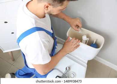 Plumber repairing toilet tank in restroom