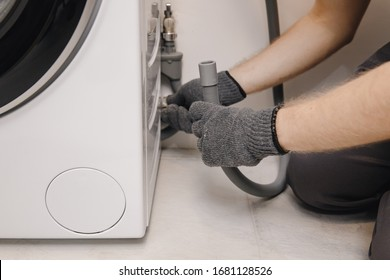Plumber repairing washing machine, working man fixing connects pipe to drain water.