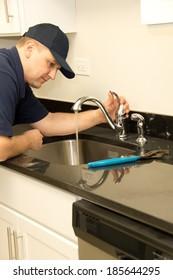 Plumber repairs kitchen faucet