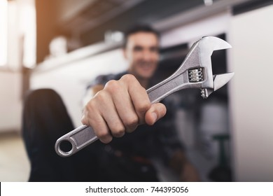 The plumber sits next to the kitchen sink on the floor and selects the appropriate spanner for repairing the pipe. He shows the wrench in the camera. The man has a special working uniform.