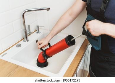 Le plombier débouge le lavabo de la cuisine avec le nettoyeur à pompe à force professionnel.