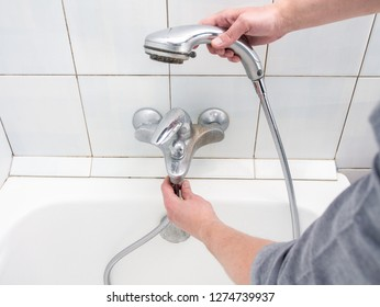 Plumber uninstalling shower hose from a bathtub faucet