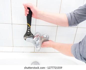 Plumber uninstalling water faucet in the bathroom