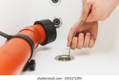 Consommation de plombier à l'aide du serpent de drainage pour déboucher la baignoire.