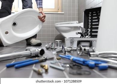 Klempner an der Arbeit in einem Badezimmer, Installations-Reparaturdienst, Montage und Installation Konzept