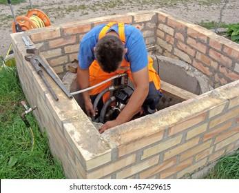 Plumber is working in opened well repairing water pump.