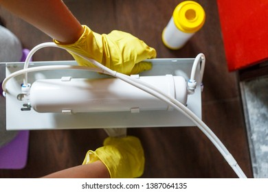 Plumber in yellow household gloves changes water filters. Repairman installing water filter cartridges in kitchen. Drinkable water filtration system in the kitchen. Clean water at home