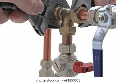 Plumber's adjustable wrenches  tightening up  copper pipework – Two adjustable wrenches tightening up a compression tee fitting to 15mm copper pipework  on a isolated white  background
